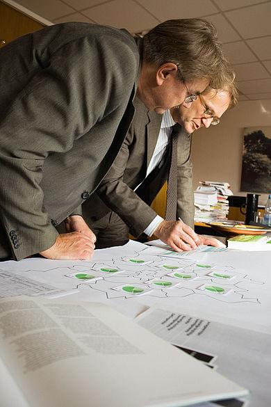 Zwei Professoren diskutieren, vor sich Unterlagen und Bücher